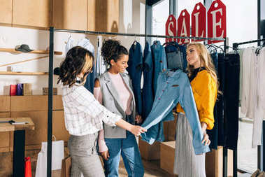 group of multiethnic shopaholics on shopping in clothing store