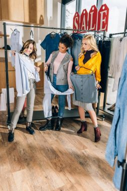 group of stylish women on shopping in clothing store