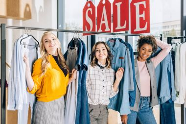 group of multiethnic young women on shopping in clothing store