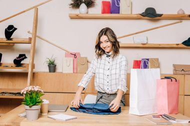 clothing store manager folding shirt to pack it into shopping bag