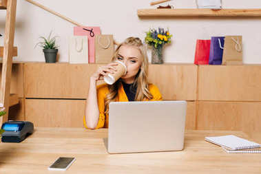 clothing store manager drinking coffee from disposable cup at workplace
