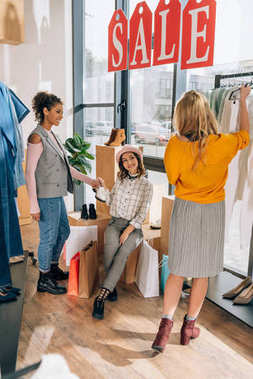 group of young women on shopping in clothing store on clearance day
