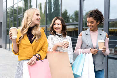 group of happy young women with shopping bags and coffee to go