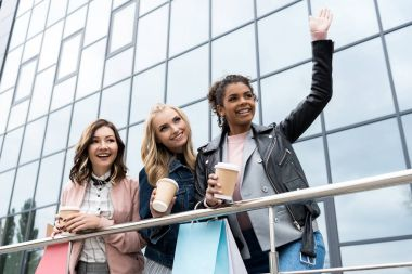 group of young women on shopping with coffee to go outdoors