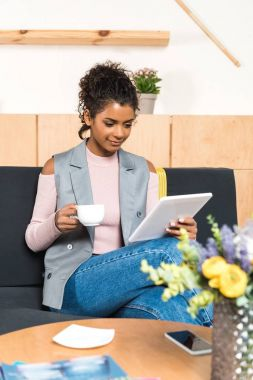 beautiful young woman using tablet and drinking coffee in cafe