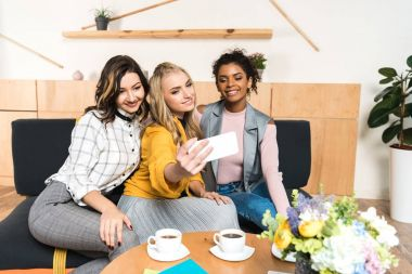group of smiling young girlfriends taking selfie in cafe