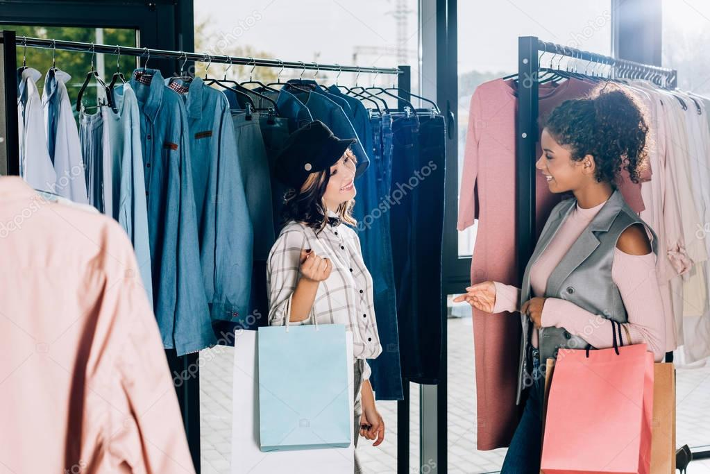young stylish women with shopping bags in clothing store
