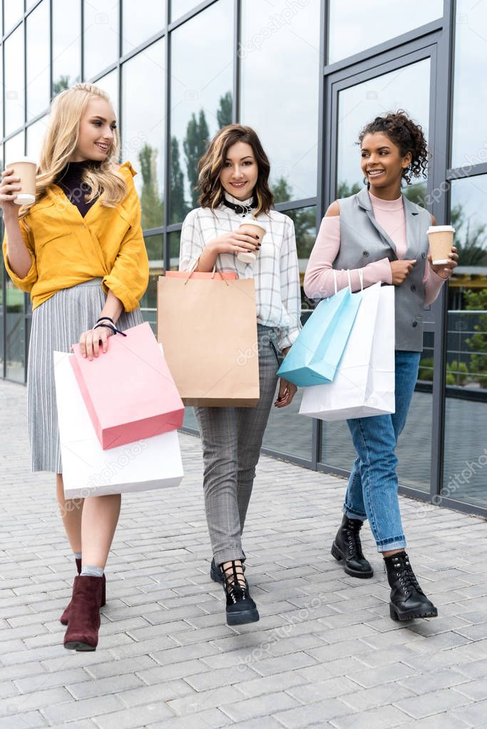 group of beautiful young women with shopping bags and coffee to go