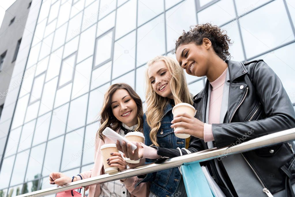 group of young girlfriends with coffee to go using smartphone together after shopping
