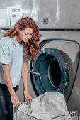 boldog női vegytisztítás munkavállaló figyelembe ruháit a mosógép