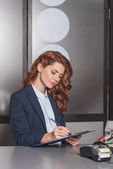 Fotografie young beautiful manageress writing in clipboard at workplace with pos terminal