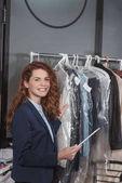 Fotografie chemické čištění šéfová pomocí tabletu před závěs s různými oblečení v pytlích