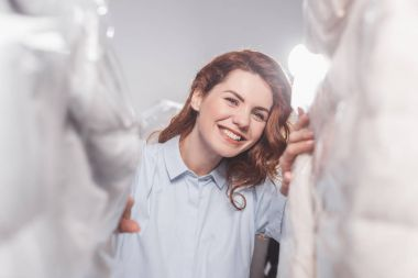 smiling female dry cleaning worker  looking at camera between clothing in plastic bags hanging at warehouse