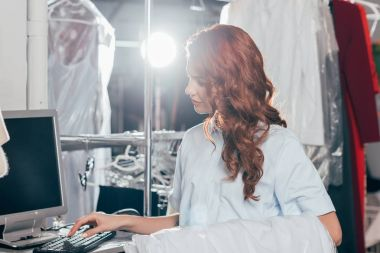 female dry cleaning worker working with computer at warehouse