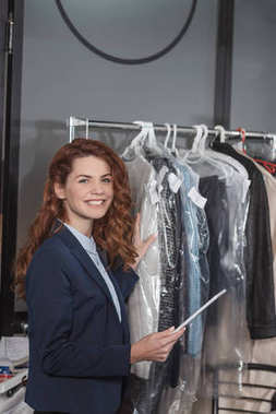 dry cleaning manageress using tablet in front of hanger with various clothing in bags