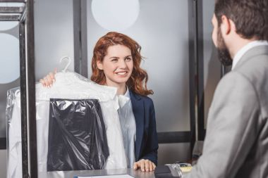 dry cleaning manageress holding bag of clothes for customer