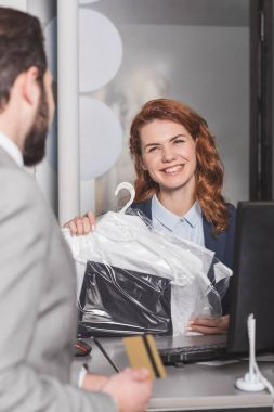 dry cleaning manageress standing at workplace with bag of clothes while customer holding gold credit card