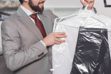 cropped shot of businessman holding plastic bag of clean clothing