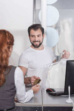 dry cleaning manager taking credit card from woman