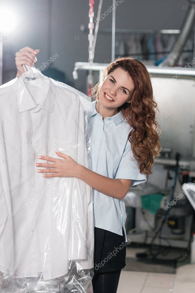 female dry cleaning worker holding clean shirt packed in plastic bag at warehouse
