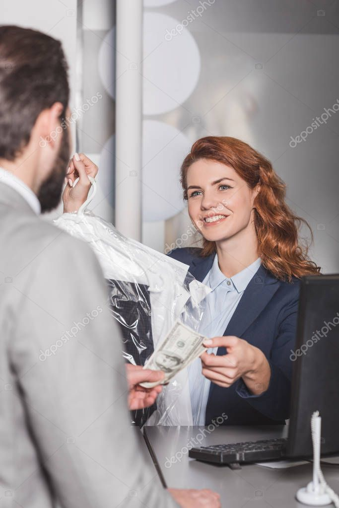 dry cleaning manageress taking cash for order from customer