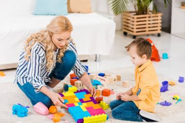 Focused mother and little son playing with toys together on floor at home stock vector