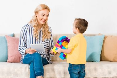 little boy showing toys to smiling mother with tablet on sofa at home