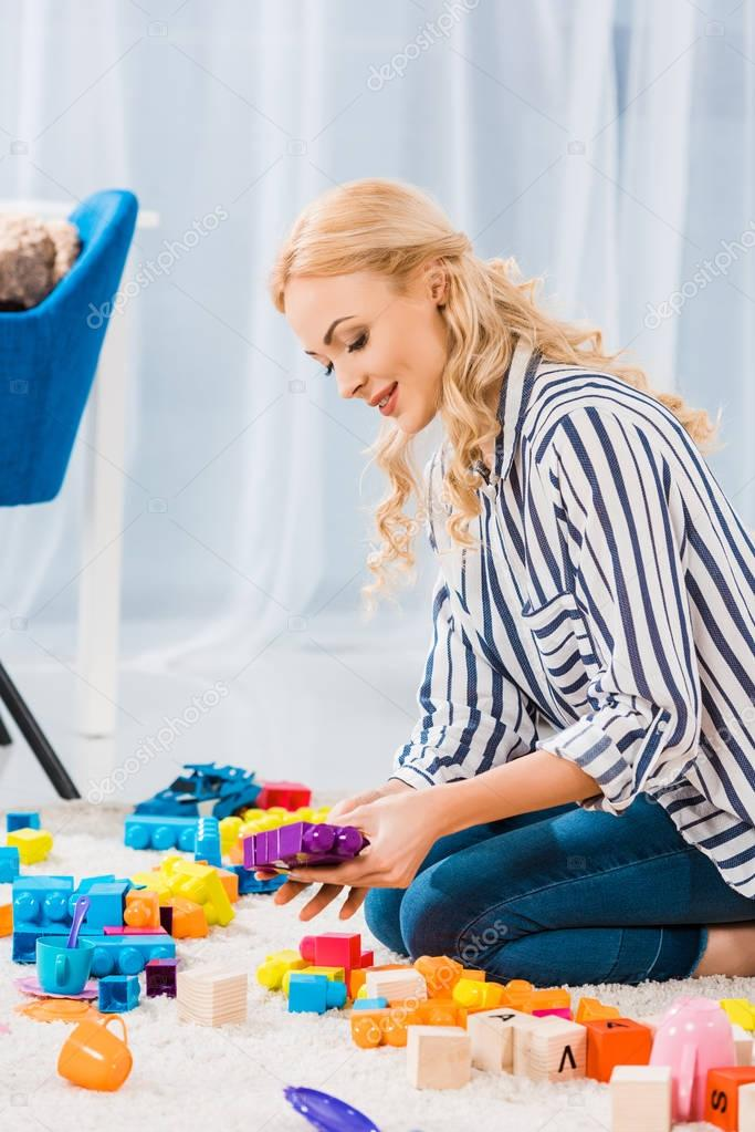 Side view of young mother with toys sitting on floor at home