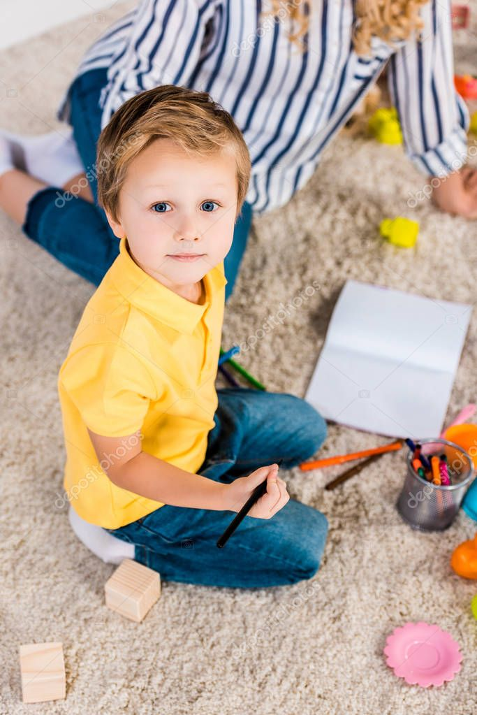 selective focus of little boy looking at camera while drawing picture together with mother at home