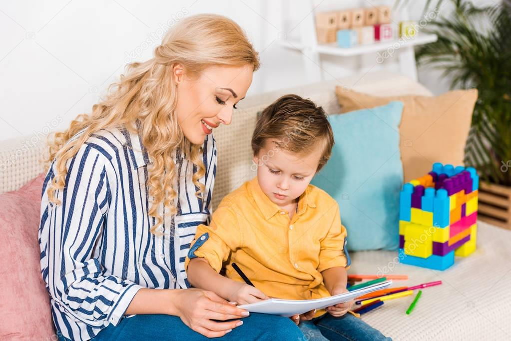 young mother and son drawing picture together while resting on sofa at home
