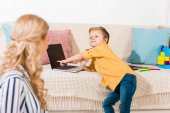 little boy pointing at laptop on sofa while mother sitting on floor at home