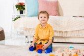 Fotografie malý chlapec při hraní s hračkami doma při pohledu na fotoaparát