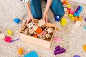 Fotografie ořízne obraz žena sběr děti hračky