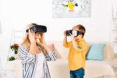 Fotografia bella madre felice e figlio utilizzando cuffie di realtà virtuale a casa