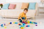 roztomilý chlapeček hraje s hračkou letadla a barevné bloky doma