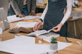 oříznutý pohled architekta čtení knihy na pracovišti s dřevěnými vzorky