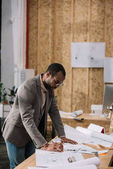 handsome african american architect drawing architectural plans at workplace