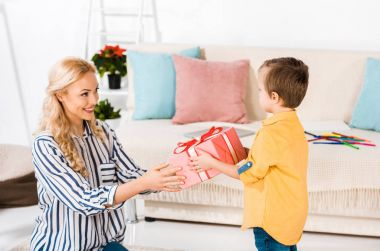 smiling mother presenting gift to little son at home