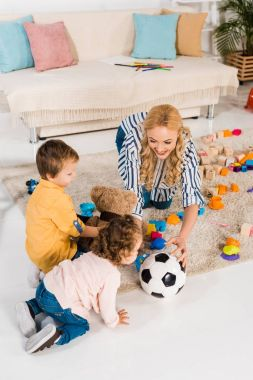 overhead view of mother playing with children wit football ball