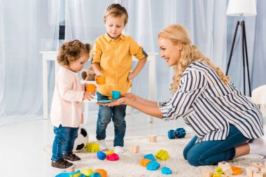 happy mother playing with son and daughter with plastic cups
