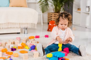 adorable child playing with plastic blocks on floor