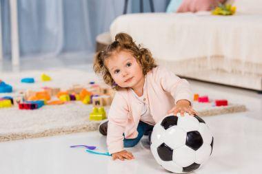 adorable kid playing with football ball