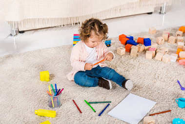 overhead view of adorable kid holding colored pencil