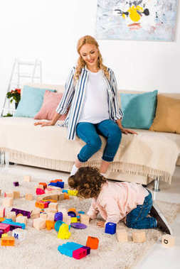 smiling pregnant mother looking how daughter playing with toys