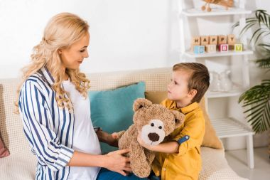 pregnant mother presenting son teddy bear