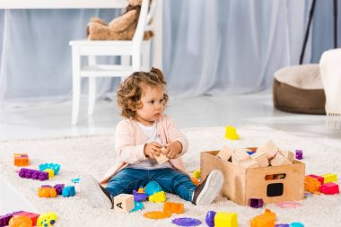 adorable little child sitting on carpet and playing with toys