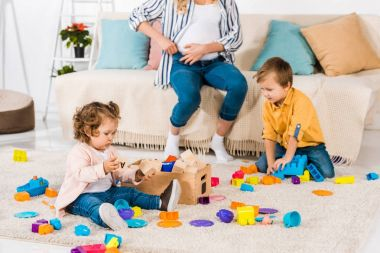cropped shot of pregnant mother sitting on sofa and little kids playing with colorful blocks at home