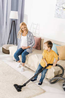 happy pregnant woman sitting on sofa and looking at cute little boy cleaning carpet with vacuum cleaner