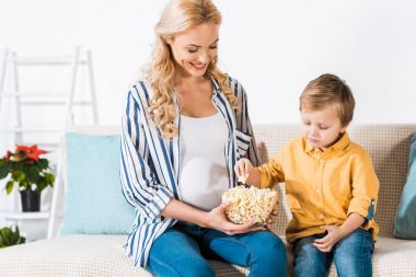 pregnant woman and cute little son eating popcorn from glass bowl at home