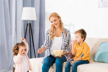 happy pregnant mother and cute little kids eating popcorn from glass bowl at home